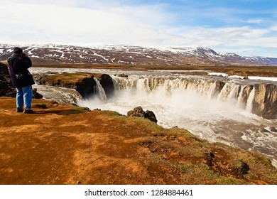 godafoss and photographer viewed at eastern bank iceland