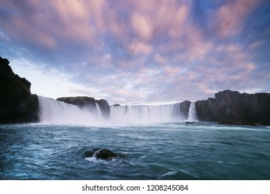 Godafoss waterfall. Famous Tourist Attraction of Iceland. Landscape with a cascade on the river and a beautiful sky at sunset