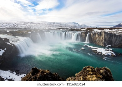 Godafoss (waterfall of the gods) is a popular tourist destination in Northern Iceland along the famous Ring Road. Icelandic Waterfall with snow capped mountains.