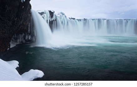 Godafoss waterfall, a majestic and powerful iconic landmark in Iceland, takes on a peaceful air after a winter snowfall, away from all the tourists
