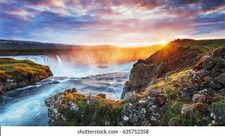Godafoss waterfall at sunset. Fantastic landscape. Beautiful cumulus clouds. Iceland