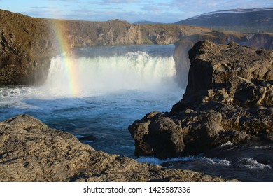 Godafoss waterfalls Iceland with rainbow and mountain range in background