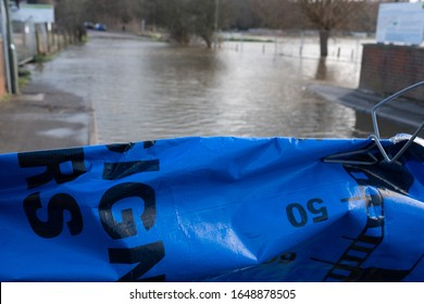 Godalming, Surrey - January 17 2020: UK Weather Flooded road in Godalming Surrey following heavy rain from storm Ciara and storm Dennis with a flood barrier