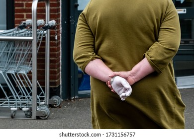 Godalming, Surrey / UK - May 13 2020: A shopper wears a single rubber glove as she waits outside a shop to ensure social distancing during the Covid19 pandemic.