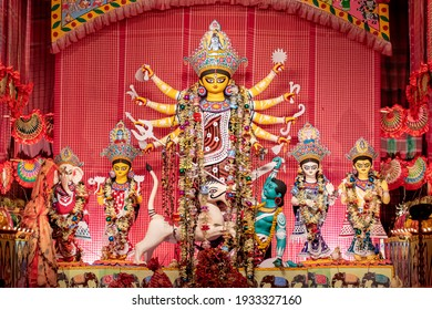 Goddess Durga idol at decorated Durga Puja pandal, shot at colored light, at Kolkata, West Bengal, India. Durga Puja is biggest religious festival of Hinduism and is now celebrated worldwide.