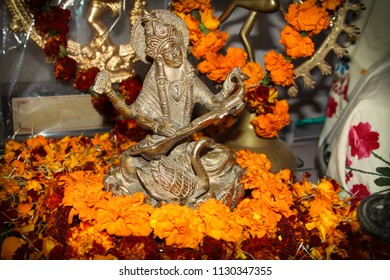 Goddess Saraswati bronze figure. Hindu puja. Incense, offerings, petals, marigold flowers. Traditional, indian, religion, holiday, Navratri, still life.