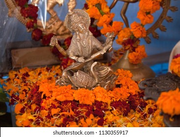 Goddess Saraswati bronze figure. Hindu puja. Incense, offerings, petals, marigold flowers. Traditional, indian, altar, religion, holiday, Navratri, still life, south asian, hinduism.