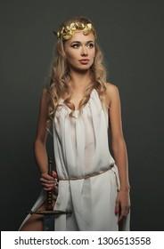goddess young woman with sword on dark bg studio shot