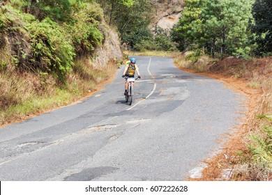 Godinez, Guatemala - December 7, 2017: Cyclist is traveling thru Guatemalan highlands near Godinez