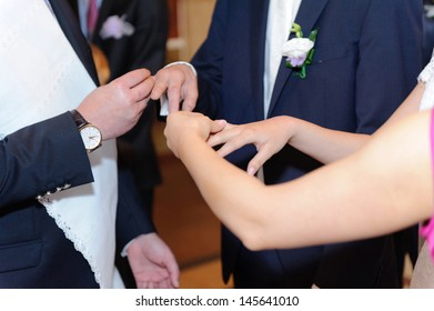 godparents exchanging rings of bride and groom