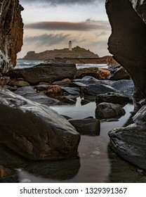 Godrevey lighthouse Cornwall viewed through the rocks.