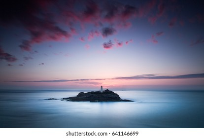 Godrevey lighthouse at sunset in Cornwall.