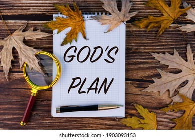 God's plan, the text is written in a white notebook with a pen on a background of autumn, maple leaves and old boards.