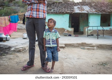 GODWAR, INDIA - 12 FEBRUARY 2015: Little boy stands next to father and looks towards him in family yard. Father not in view.