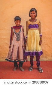 GODWAR REGION, INDIA - 15 FEBRUARY 2015: Two Indian girls wear beautiful dresses and pose in front of wall on red carpet. Post-processed with grain, texture and colour effect.