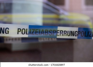 """Goerlitz Germany - april 11, 2020: Cordon tape with the word """"Polizeiabsperrung"""", the german word for police cordon, in the background a police car"""