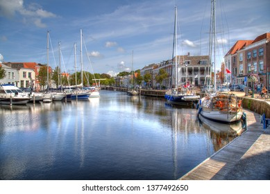 Goes, The Netherlands - August 24, 2017: Recreational sailboats lie moored and people sit on benches in the old harbor of Goes, The Netherlands on August 24, 2017
