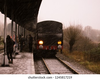 "GOES, THE NETHERLANDS - DECEMBER 27, 2014: In the snow passengers are  boarding the historical steam engine ""4389 from the USA Army Transportation Corps"" to make a roundtrip."