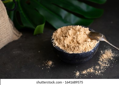 Gofio, Canarian flour made from different roasted grains on concrete background with tropical leafe. This is important ingredient of many dish of Canary Islands Cuisine.