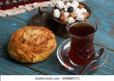 Gogal and glass of black tea with traditional snack in copper bowl, on rustic wooden table. Azerbaijan national Novruz holiday pastry