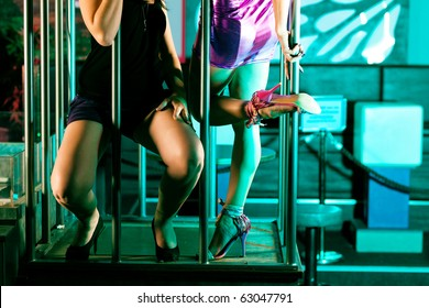 Go-go dancer in a cage in disco or nightclub, two women