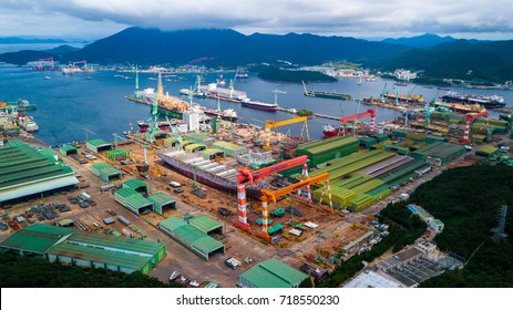 Gohyeon, South korea - September 2017 : High angle view of Samsung shipyard in Gohyeon, South korea. Scenery consist of shipyard inside the bay, commercial ship, platform, heavy crane and building.
