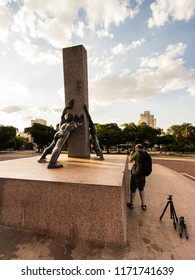 GOIANIA, BRAZIL - SEPTEMBER 01, 2018:Photographer in action at Monument Of Three Human Races is the name this statue exposed in In Civic Square of Goiania city. On September 01, 2018, Goiania, Brazil.