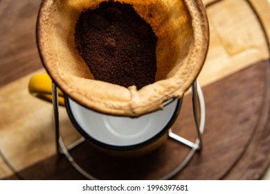 GOIÂNIA GOIAS BRAZIL - JUNE 24 2021:  Coffee powder in fabric strainer with a mug below. Preparing breakfast.