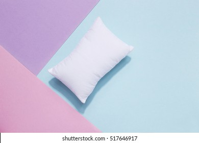 Going to bed, falling asleep. Top view of white pillow on serenity blue background and pink pastel
