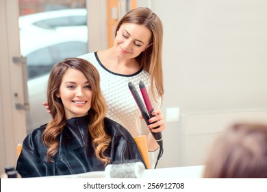 Going for big curls. Mirror reflection of a young beautiful woman discussing hairstyling with her hairdresser while sitting in the hair salon and getting her hair done with hair iron