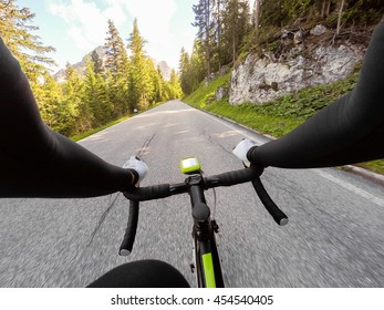 Going up by road bike on mountainous road in a sunny day. Cycling in Dolomites, Passo Falzarego. POV Original point of view