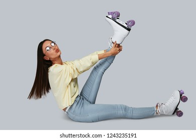Going crazy. Beautiful young Asian woman stretching her leg and puckering while sitting against grey background