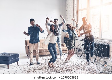 Going crazy. Full length of happy young people dancing while spending time at home with confetti flying everywhere
