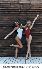 Going crazy. Full length of two attractive young women in swimwear smiling and gesturing while posing against the wooden wall outdoors