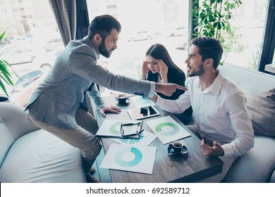 Going crazy and insane, stress and agression. Angry young brunet bearded entrepreneur is pointing at his partner, blaming him, they sit in a cafe, wearing formal wear