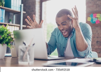 Going crazy at work. Young mulatto entrepreneur is shocked of the fail he has in business, he is yelling and gesturing like crazy
