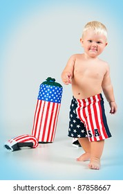 Going cute smiling baby in boxer shorts with  boxing gloves and pear