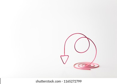 Going down or decreasing. arrow spiraling downward for something decreasing. Red wires forming a downward arrow. Plenty of copy space on left. (flip image for reversed space). presentation background.