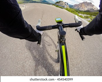 Going down on mountainous road in a sunny day. Cycling in Dolomites, Passo Valparola. POV Original point of view