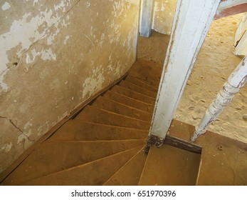 Going down a stairway of an abandoned house, being reclaimed by the desert and covered with sand.