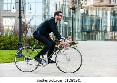 Going everywhere by his bike. Side view of young businessman looking forward while riding on his bicycle