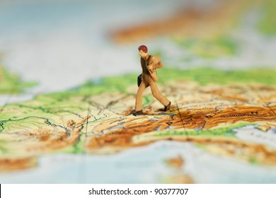 Going The Extra Mile In Business, macro of a miniature model businessman with briefcase striding across a map, concept with shallow DOF.