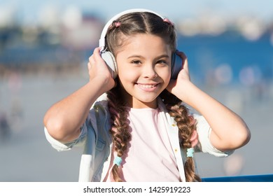Going with the flow. Adorable headset user. Small child wearing adjustable white headset. Little girl using wireless bluetooth headset outdoor. Cute kid listening music in stereo headset.