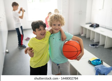 Going to gym. Two smiling school boys standing together laying hands upon each others shoulders in a changing room.