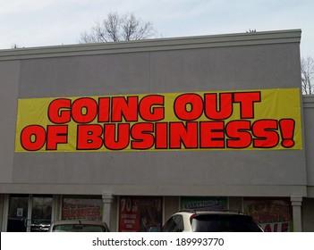 Going Out of Business.  A going out of business banner on a bankrupt storefront.