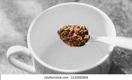 Going to prepare a instant black coffee. Pouring granulated coffee into the coffee cup.