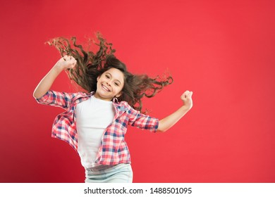 Going to prom. Cute small girl with wavy prom hairstyle on red background. Adorable little child with long curly brunette hair for junior prom. Having good time at prom night, copy space.