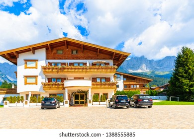 GOING AM WILDEN KAISER, TIROL - JUL 30, 2018: Traditional alpine hotel in village of Going am Wilden Kaiser on beautiful sunny summer day with Alps mountains in background, Tirol, Austria.