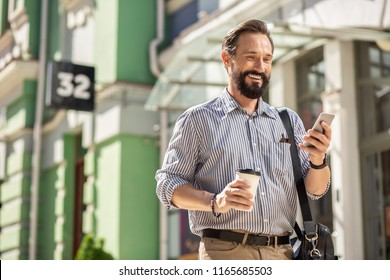 Going to work. Positive adult man smiling while using his smartphone