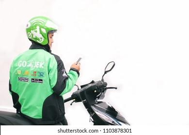 gojek or grab man looking smartphone sitting on the motorcycle. Yogyakarta Indonesia. june 03, 2018